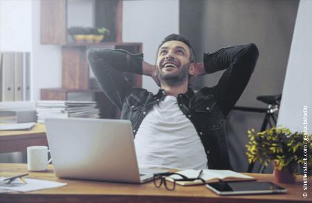 Ein junger Lehrer sitzt entspannt am Schreibtisch. Er hat die Hände im Nacken verschränkt und lächelt zufrieden, sein Blick ist nach oben Gerichtet