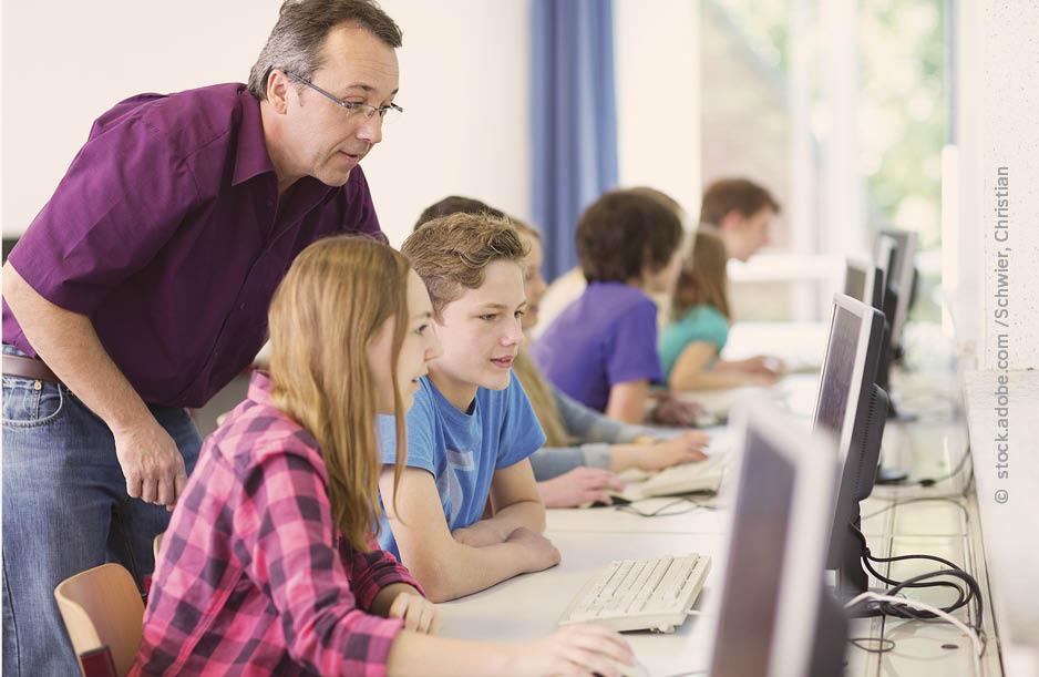Ein Lehrer sieht drei Schülerinnen über die Schulter. Sie sitzen vor einem PC Bildschirm und arbeiten digital