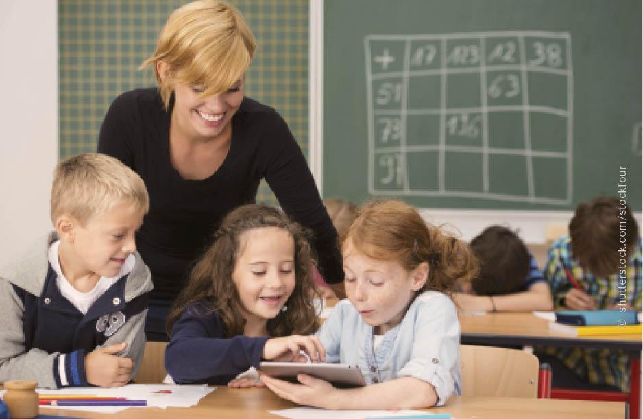 Eine Lehrerin steht lächelnd im Klassenraum hinter drei Schülerinnen, die ein Tablet bedienen